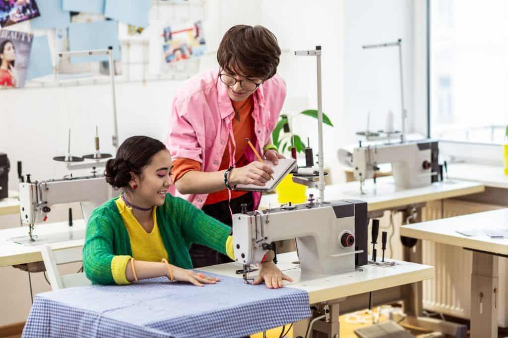 Homem e mulher asiáticos conversando, mulher está operando uma máquina de costura e ele está ao lago com um caderno e lápis na mão.