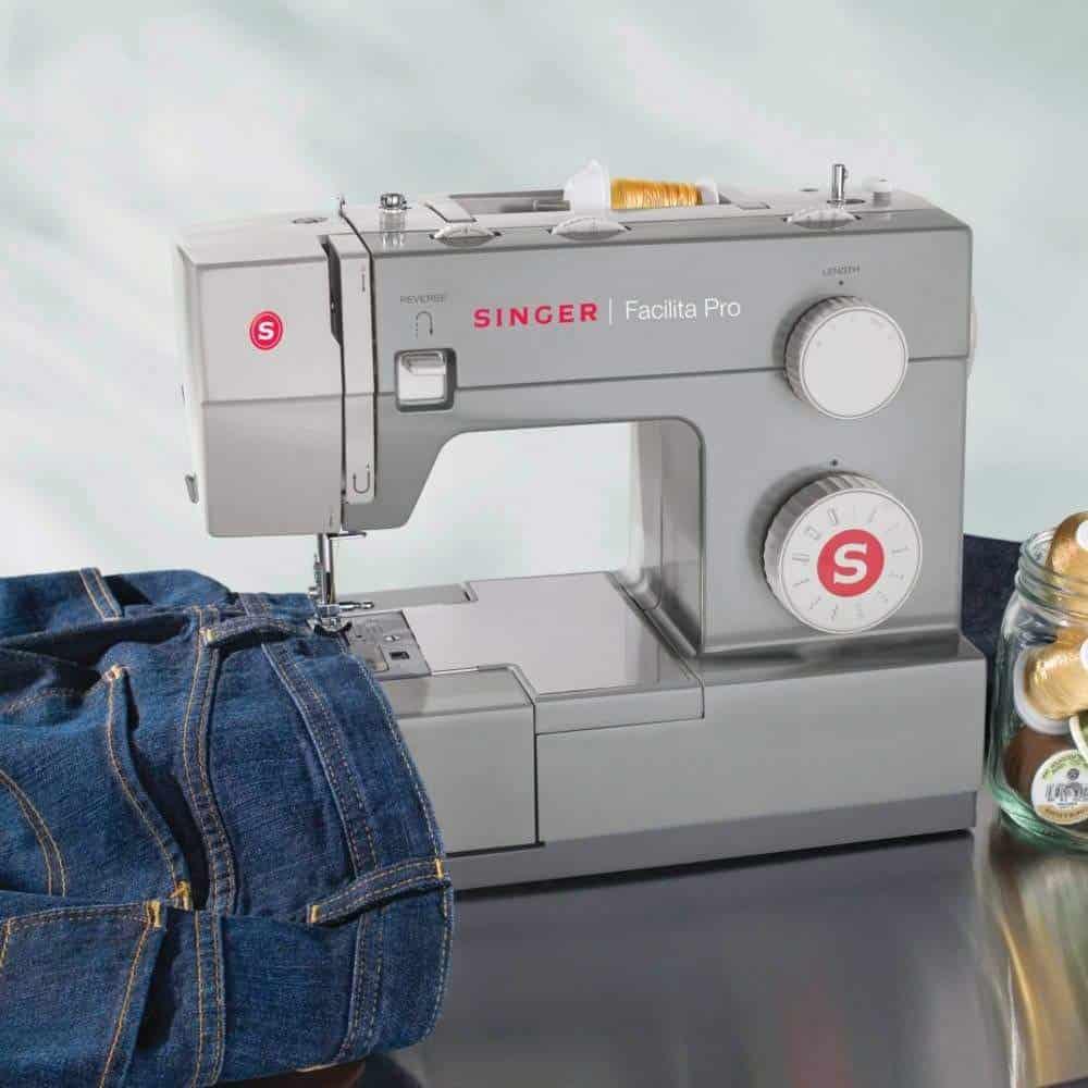 Máquina de costura Singer mecânica, costurando calça jeans.