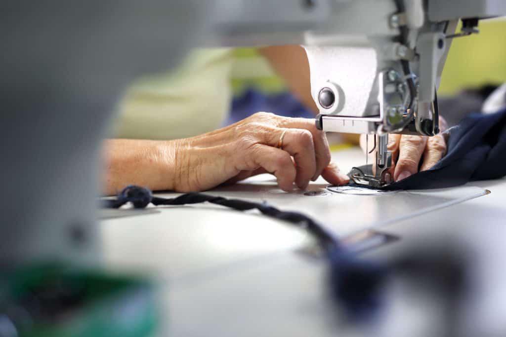 Imagem de pessoa costurando roupa.