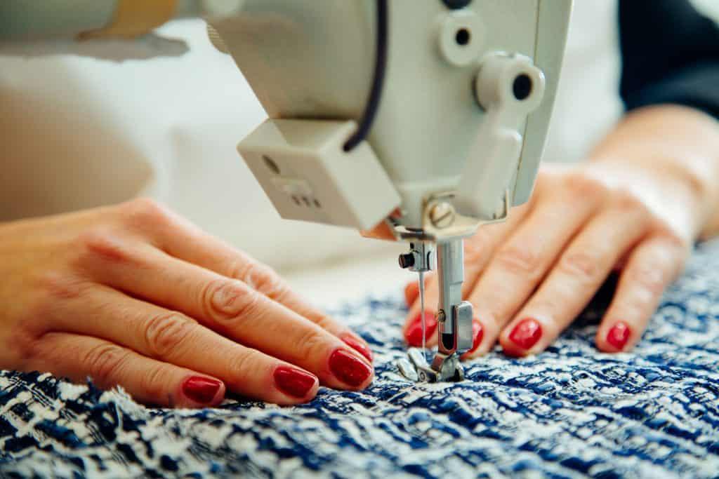 Mãos de uma mulher costurando tecido em máquina de costura.