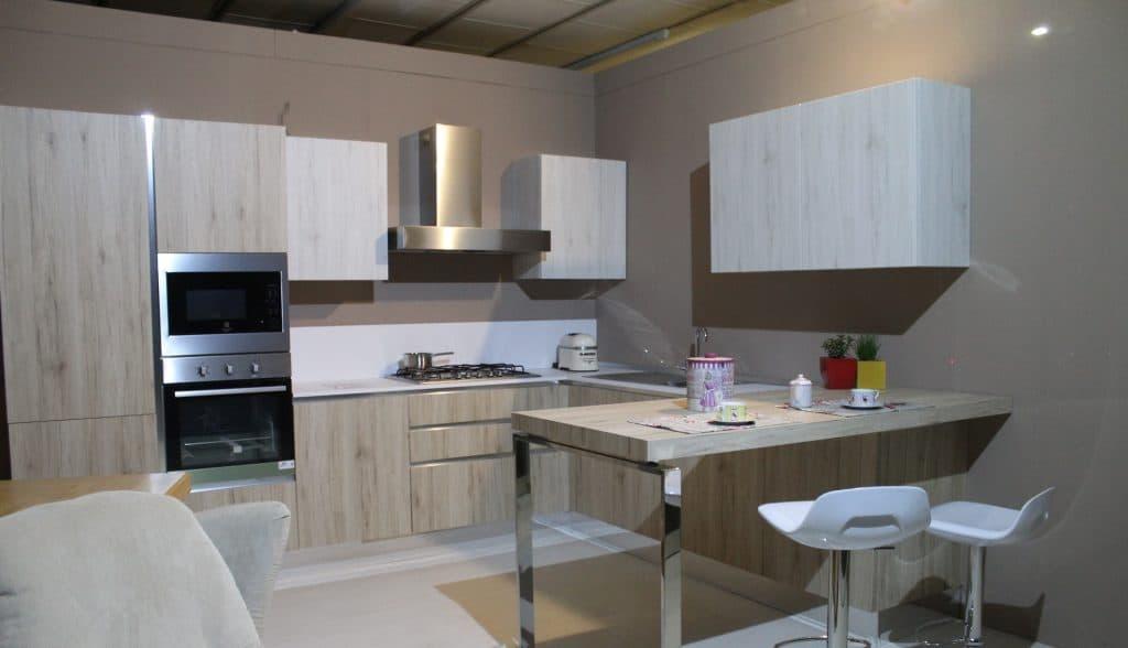 Imagem de cozinha mobiliada bege e branca.