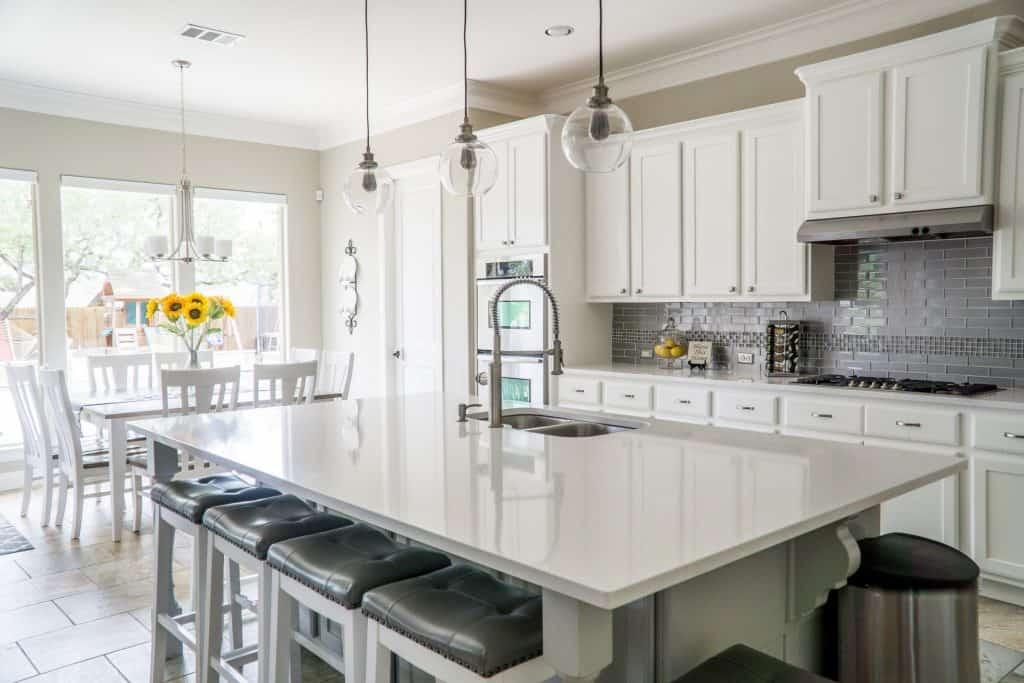 Imagem de cozinha com móveis e paredes brancos.