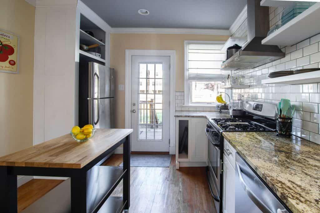 Na foto uma cozinha branca com detalhes em madeira.