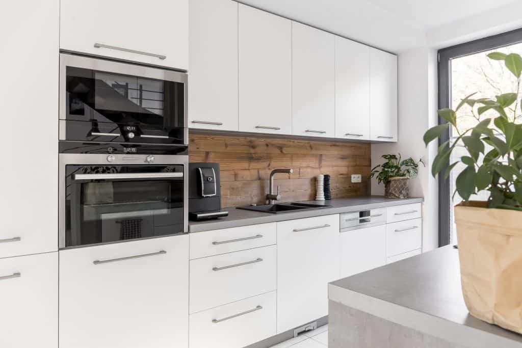 Cozinha moderna com móveis e forno de embutir.