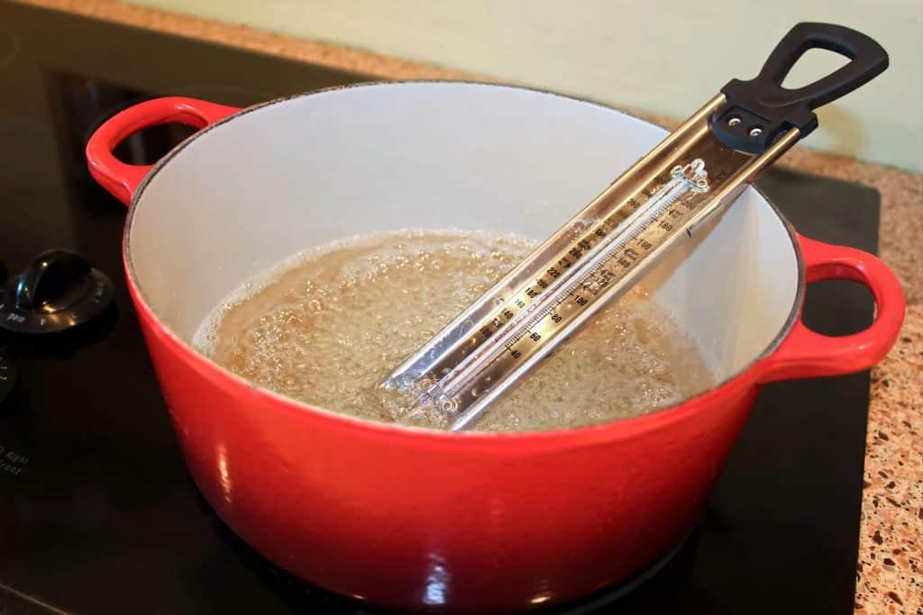 Foto de uma panela vermelha em fogão de indução com ingrediente em fervura e termômetro culinário dentro.