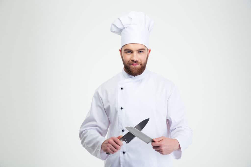 Imagem de cozinheiro com facas na mão.