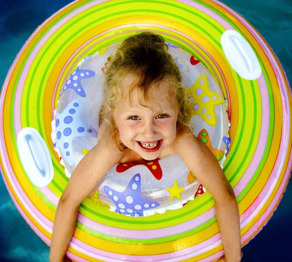 Criança na boia em uma piscina.