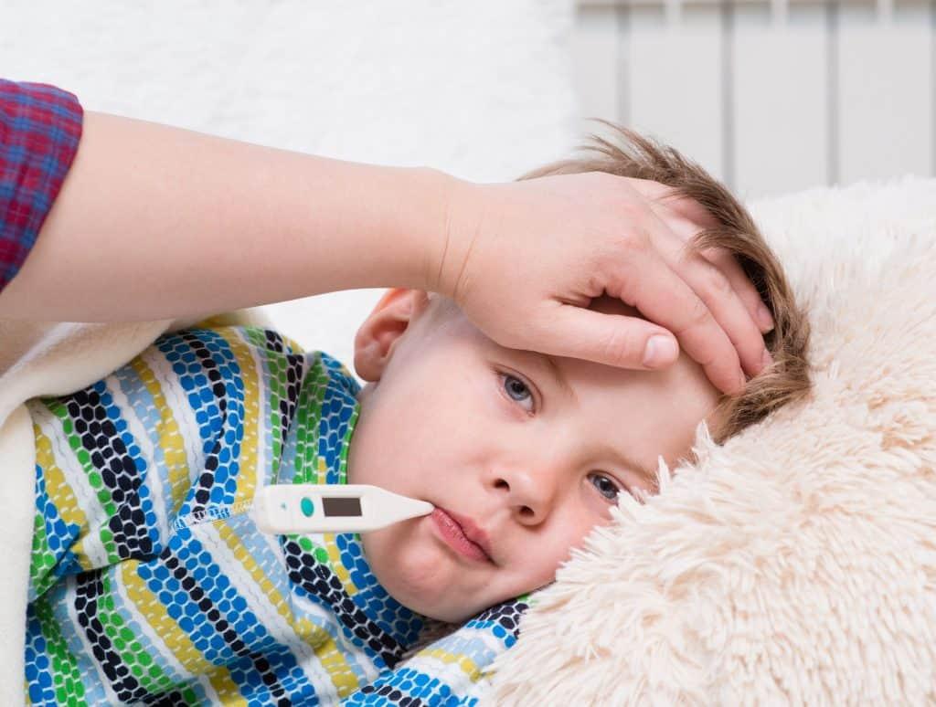 A imagem mostra um menino doente com termômetro na boca e sua mãe com a mão sobre a testa dele.