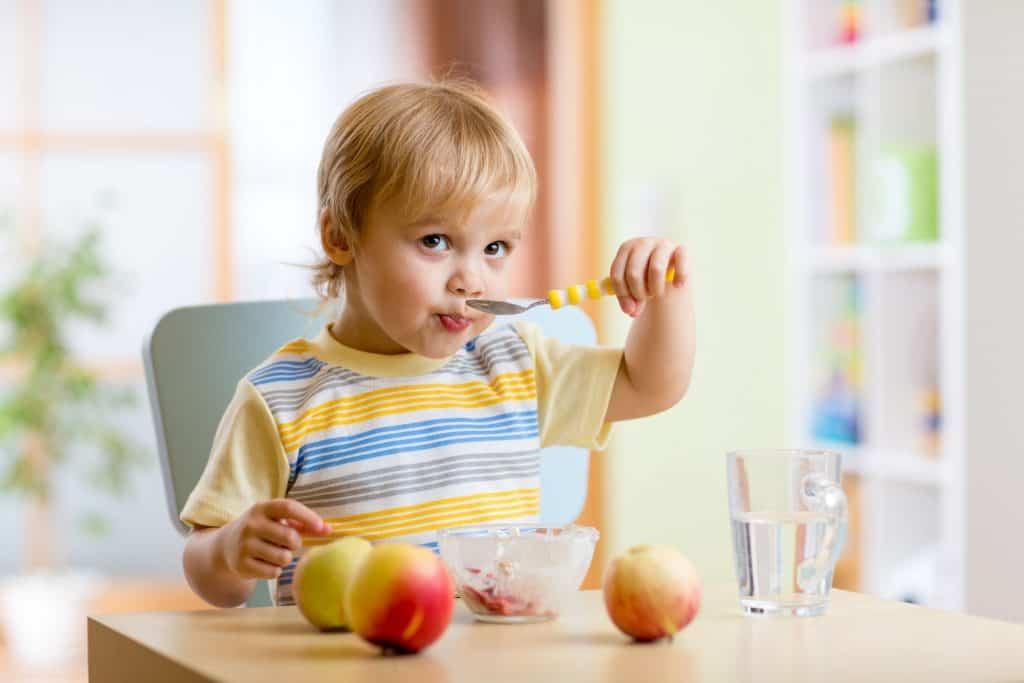 Imagem de um menino comendo sozinho com uma colher.