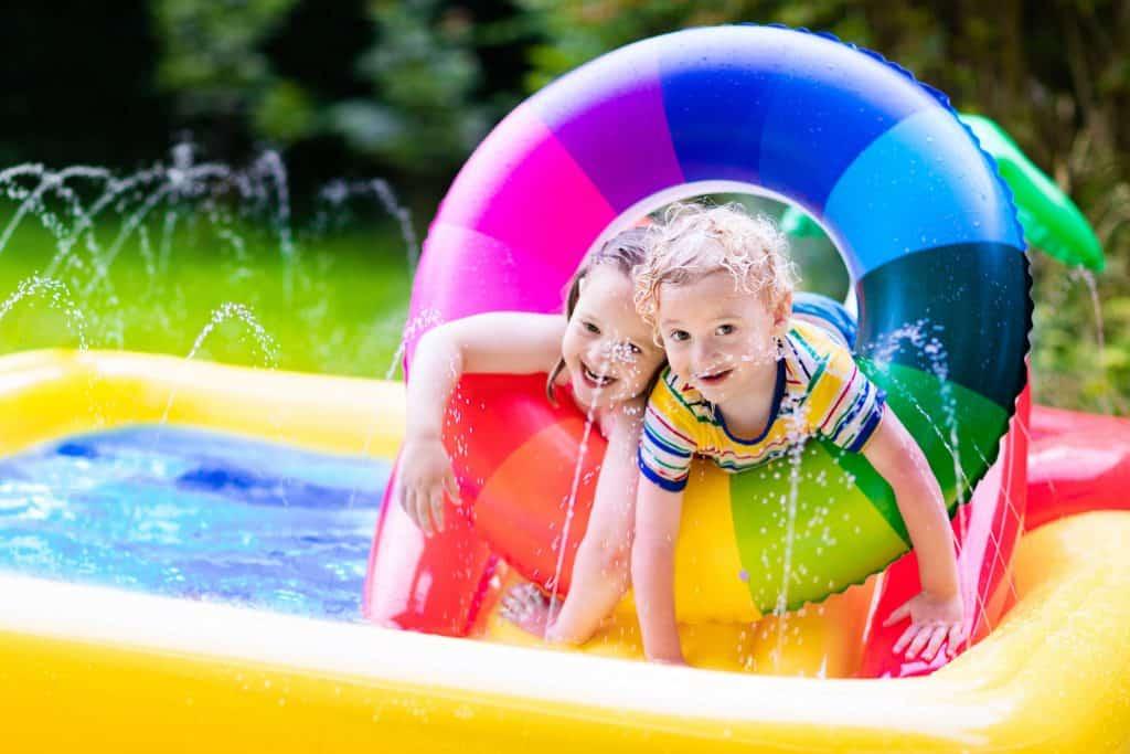 Crianças brincando com bóia em piscina inflável.