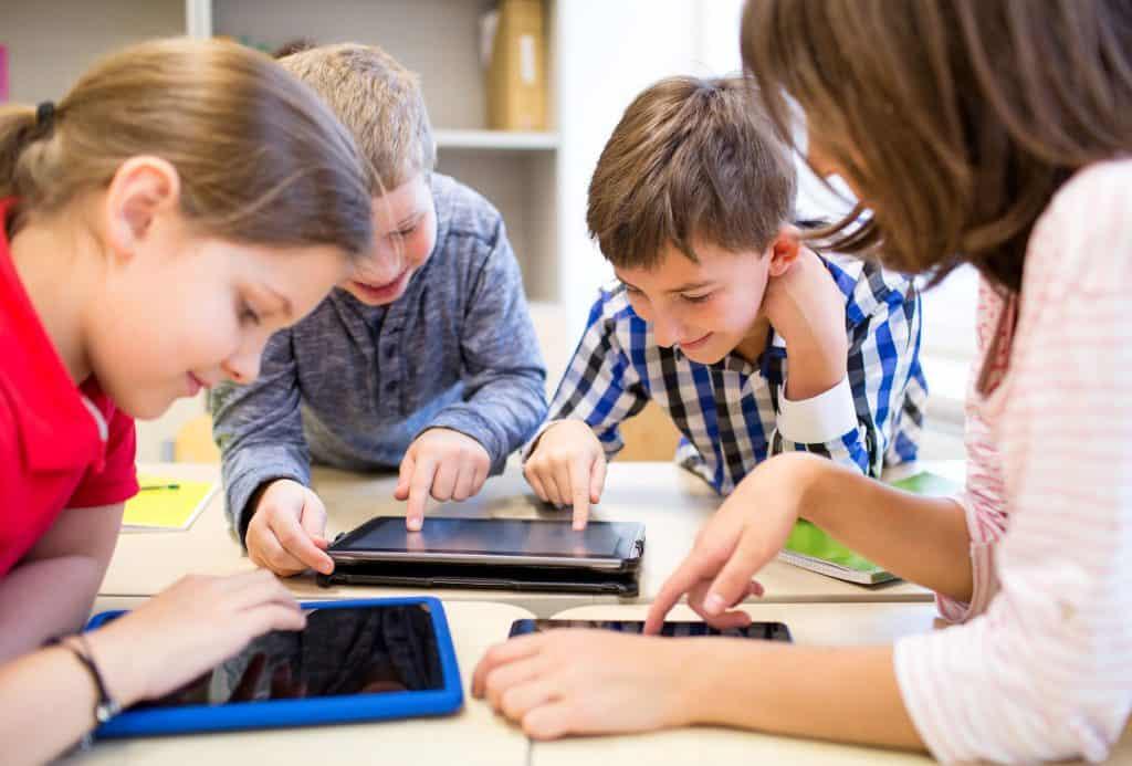 Foto de crianças usando um tablets.