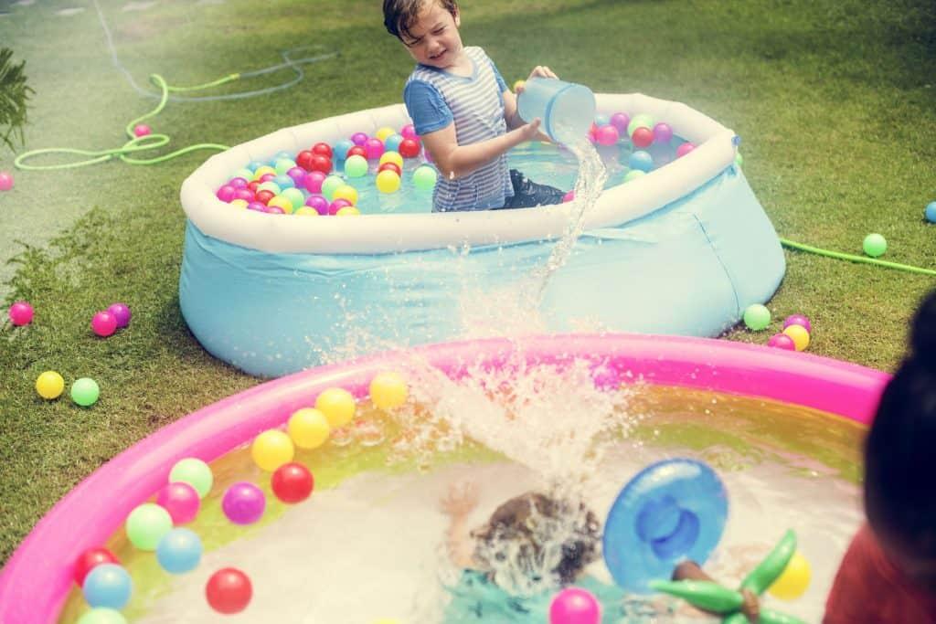 Crianças brincando em piscinas infláveis.