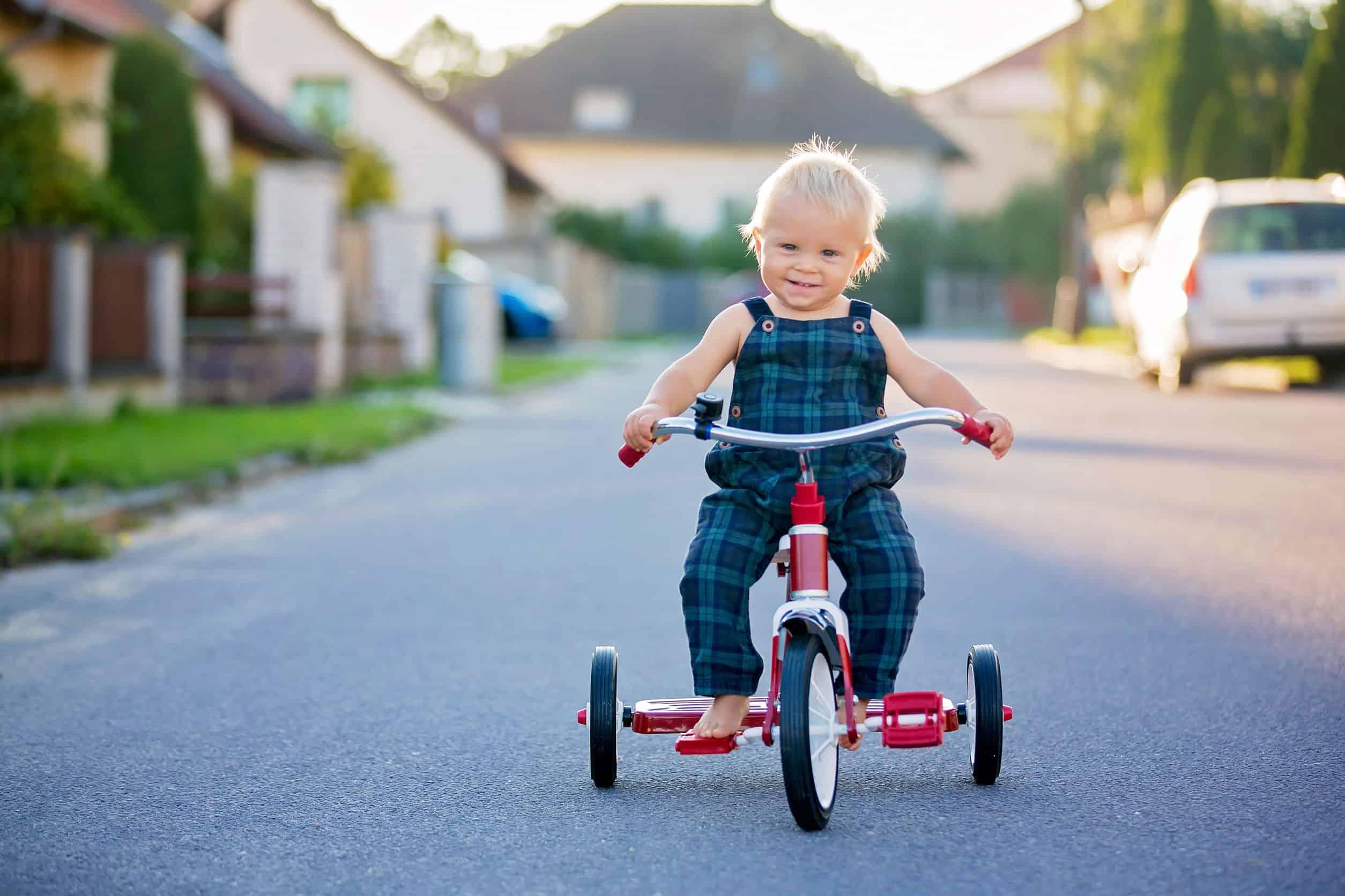 Criança pedalando no triciclo infantil na rua.