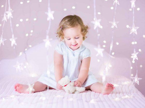 Na foto uma menina de vestido branco sentada em uma cama com luzinhas em formato de estrela ao redor dela.