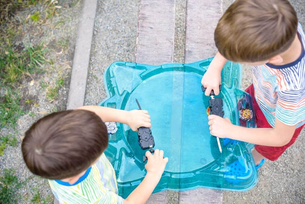 Duas crianças jogando Beyblade.