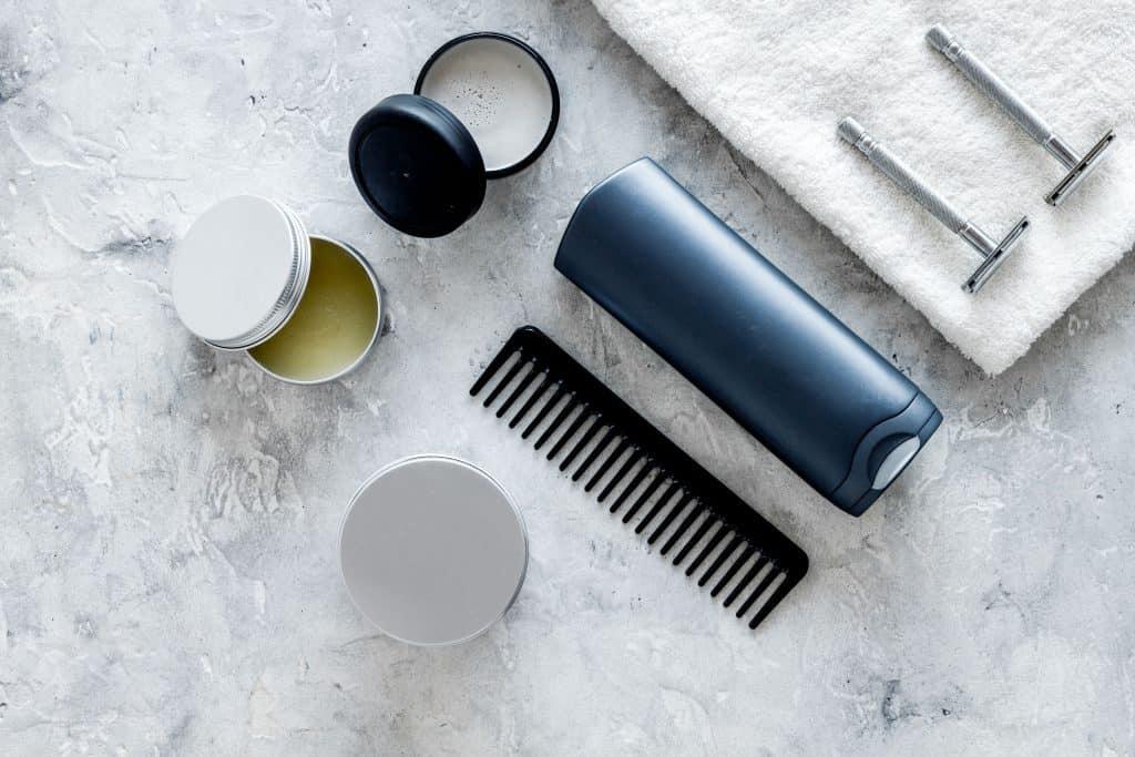 Cera modeladora para cabelo em cima da mesa com outros itens de cuidado pessoal.