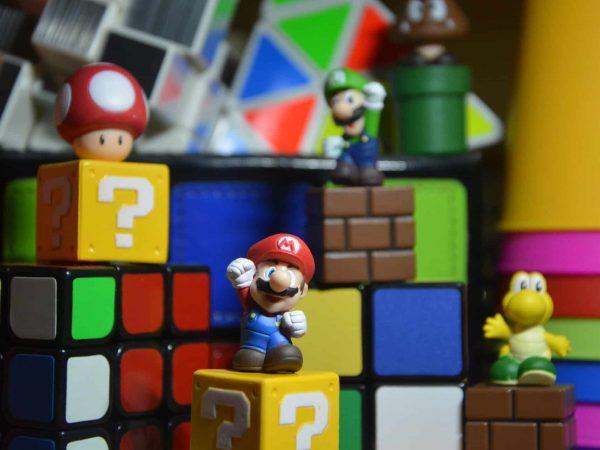 Na foto alguns personagens do Super Mario World em cima de cubos de montar.