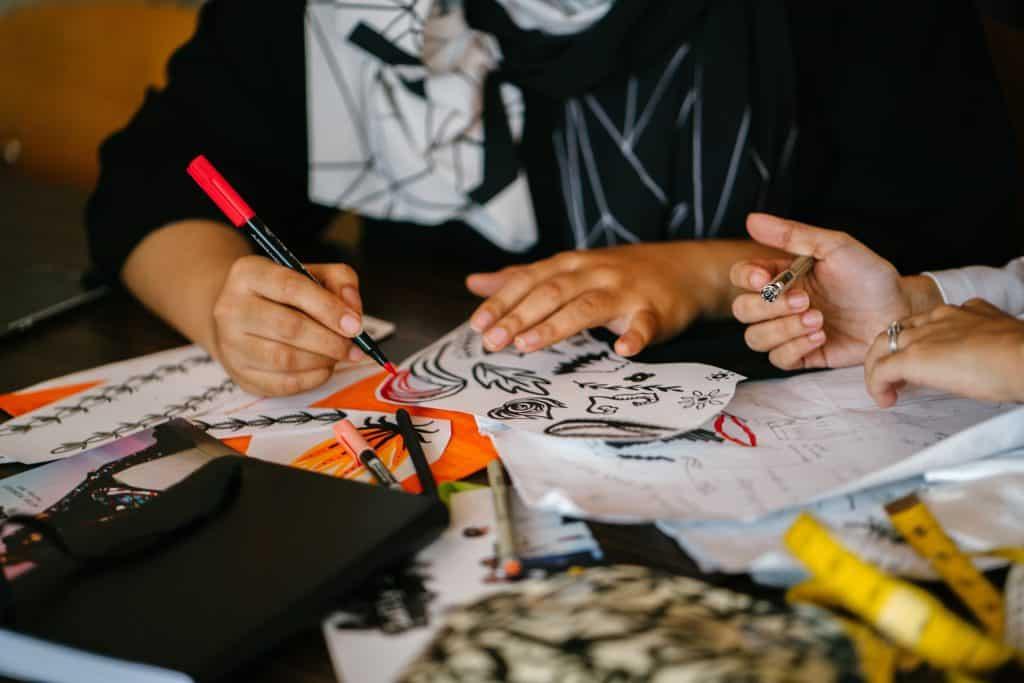 Foto de duas pessoas ao redor de uma mesa colorindo em papéis usando canetas hidrocor. Na mesa é possível observar diversos papéis e canetas.