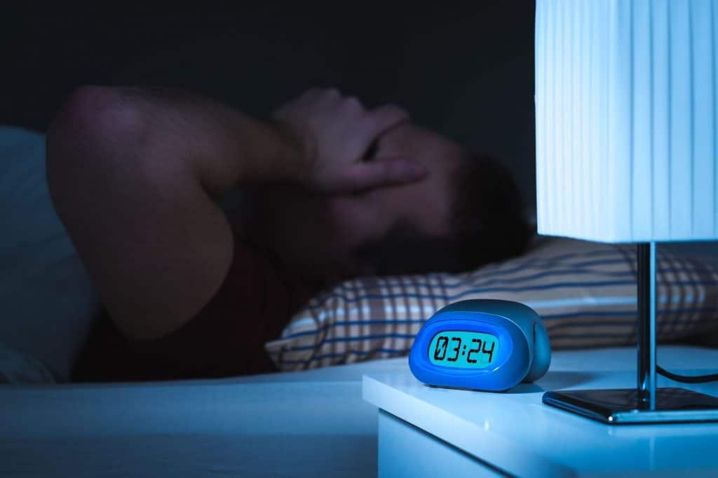 Uma pessoa com insônia deitada em uma cama ao lado de um criado-mudo com um abajur apagado e um despertador digital na cor azul.