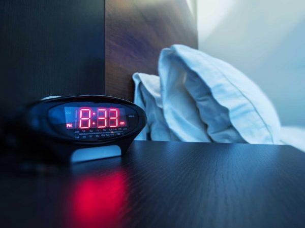 Um rádio relógio despertador em cima de um criado mudo ao lado de uma cama.