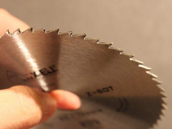 Um disco de serra circular na mão de uma pessoa.