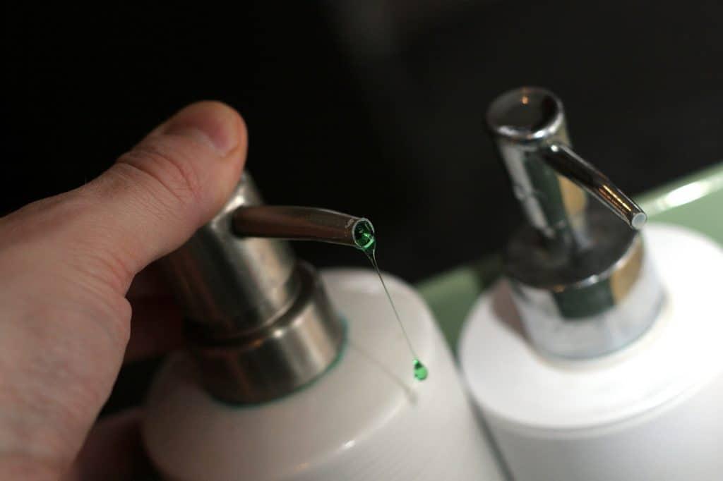 Mão pressionado frasco de sabonete líquido.