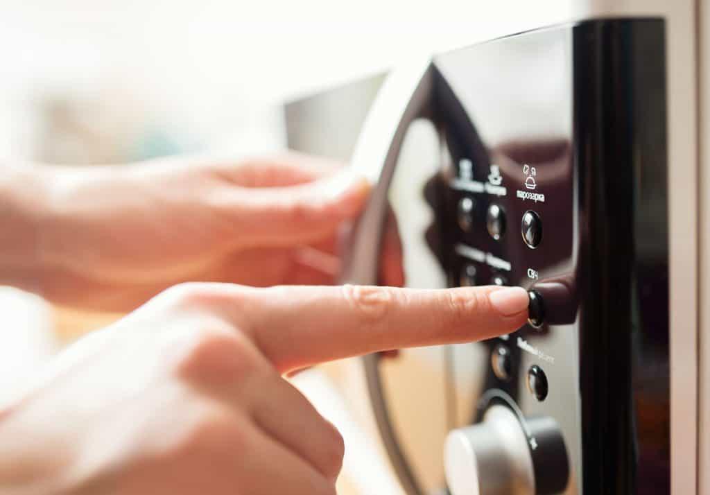 Imagem de pessoa apertando em botão em micro-ondas.