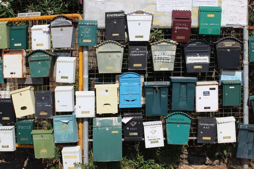 Parede com várias caixas de correio de diferentes materiais.