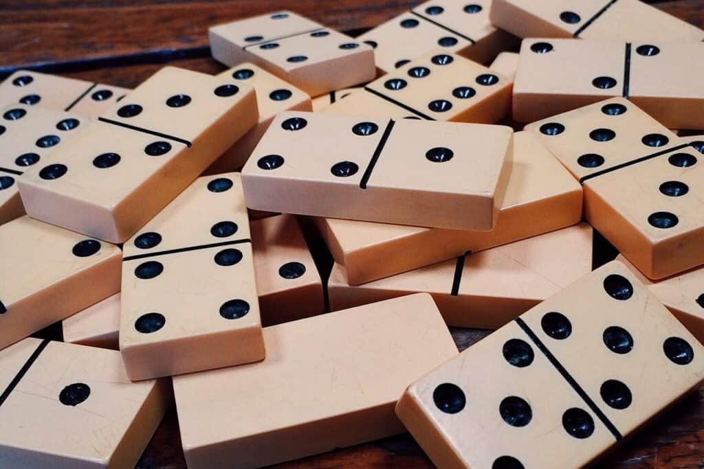 Imagem mostra peças de dominó amontoadas aleatoriamente, sendo a maioria com suas faces numéricas voltadas para cima.