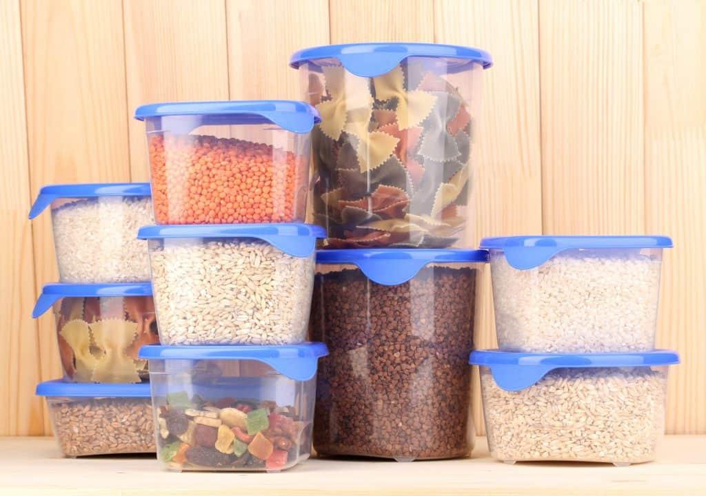 Vários potes de plástico com alimentos armazenados.