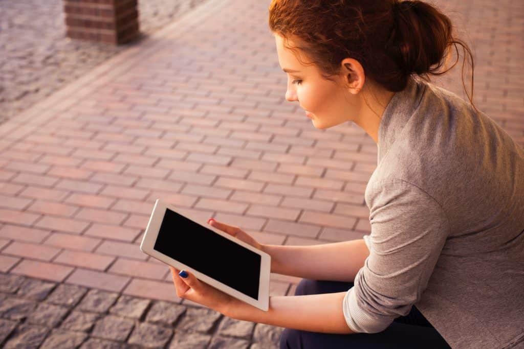 Imagem de mulher sentada com um tablet nas mãos.