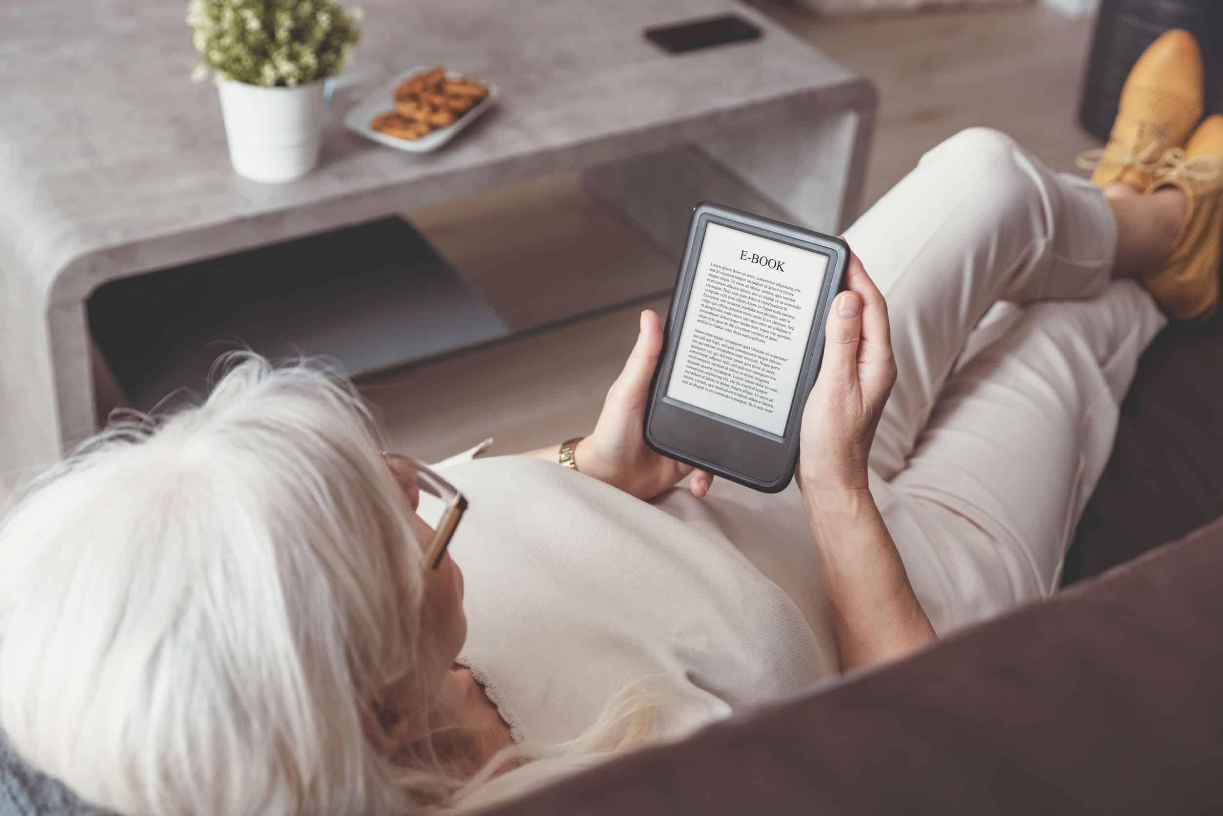 Na foto uma mulher deitada em um sofá lendo em um e-reader.