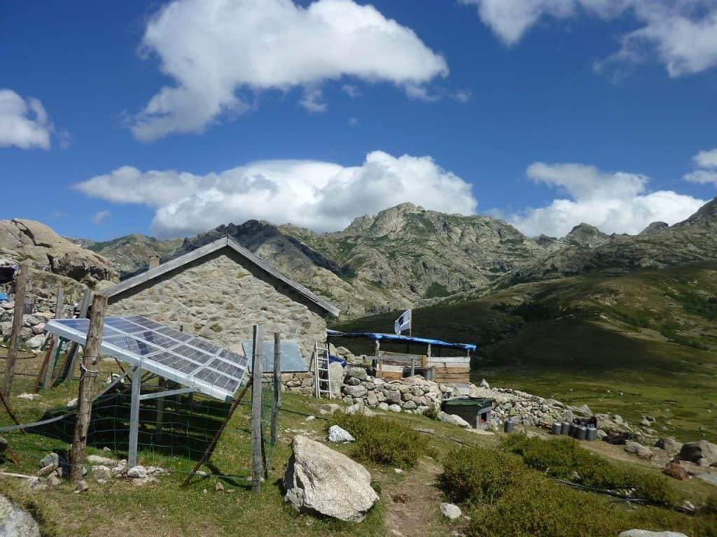 Fotografia de uma casa nas montanhas, feita de pedras com um sistema de painéis solares instalado ao lado, cercado por tela de arame.