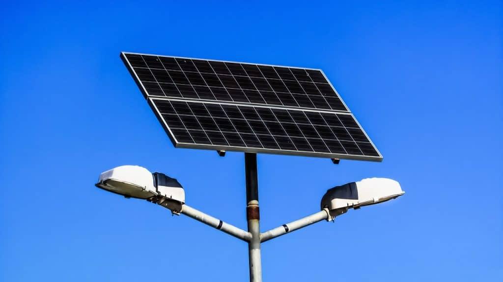 Fotografia de dois painéis solares presos a um poste, com duas lâmpadas voltadas para diferentes direções.