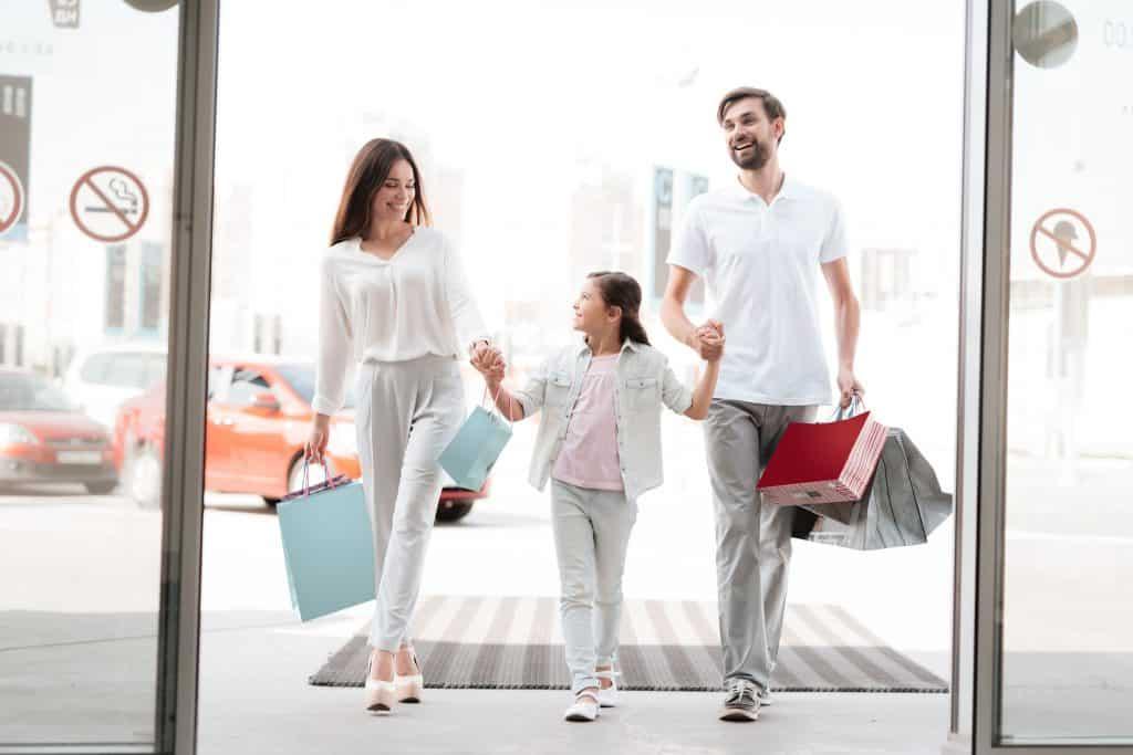 Imagem mostra uma família entrando em uma loja.