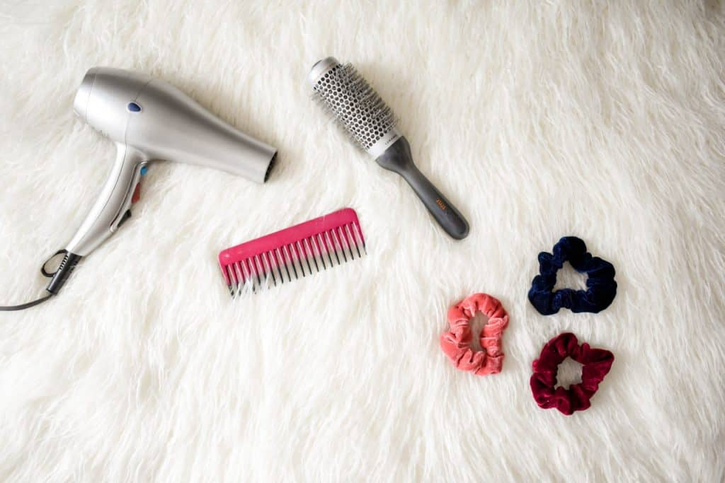 Foto de um secador, um pente, uma escova e três prendedores de cabelo em cima de um tapete branco de pelinhos.