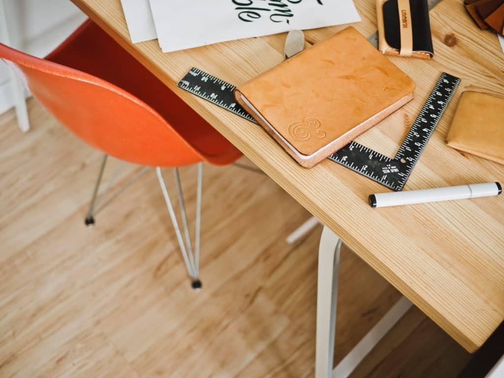 Imagem mostra um esquadro sob uma escrivaninha, parcialmente encoberto por uma caderneta e rodeada de outros itens de escritório.