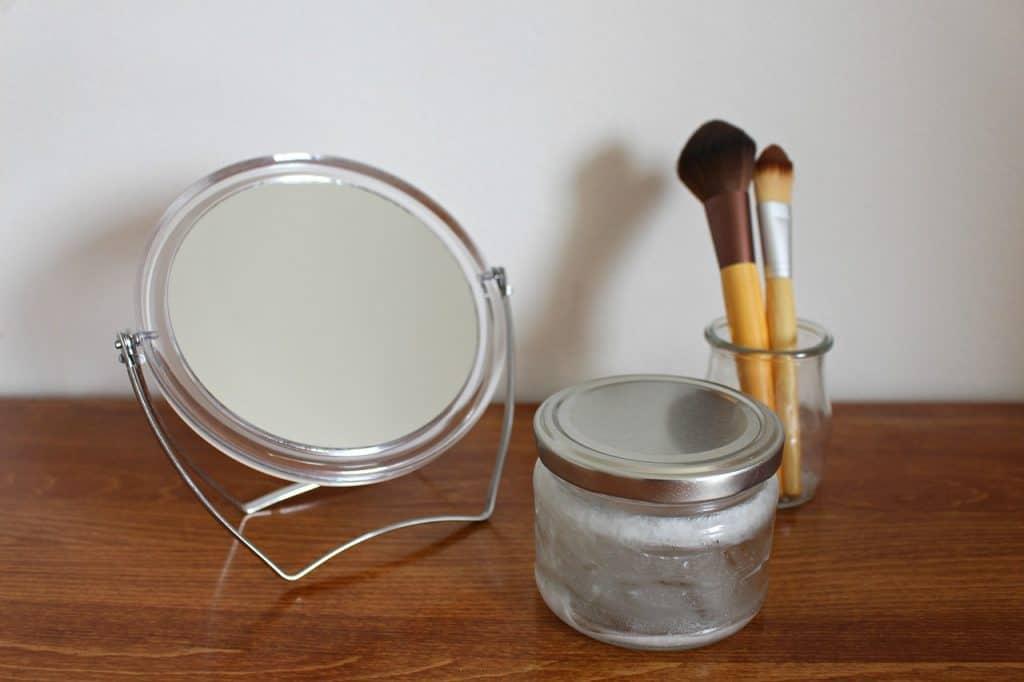 Frasco de óleo, com pincel de maquiagem e espelho.