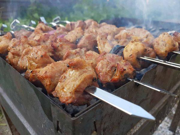 Vários espetos com carne em cubos assando enfileiradas em churrasqueira.