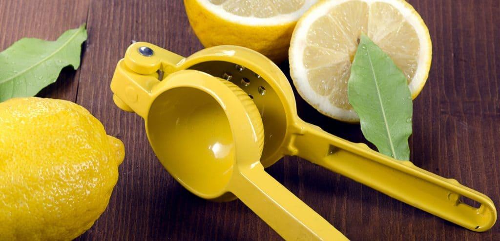 Imagem de espremedor amarelo e limões.