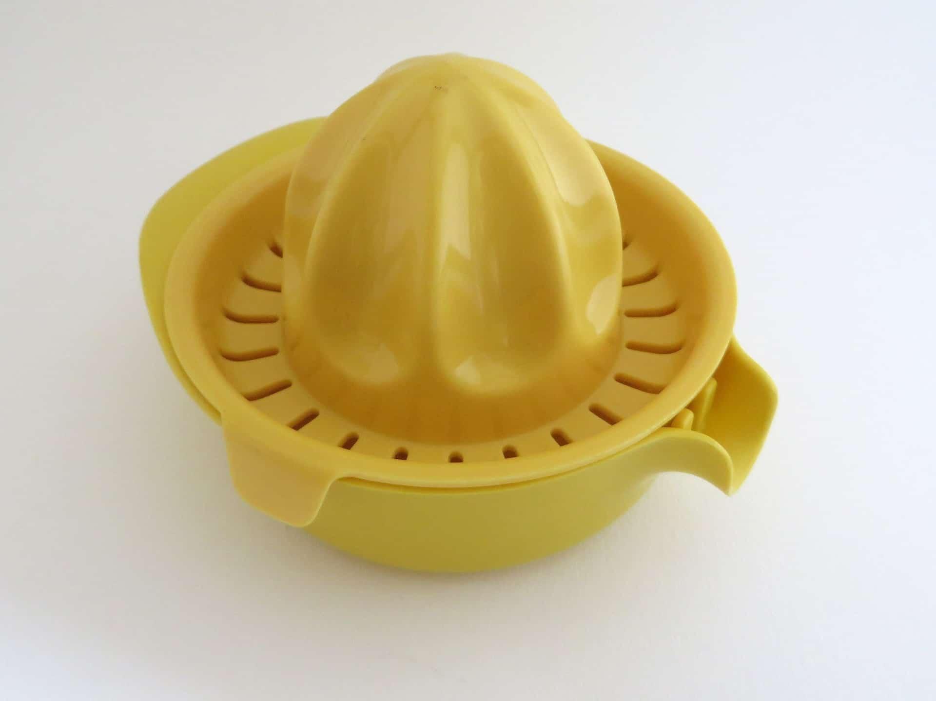 Espremedor de limão amarelo de plástico em um fundo branco.