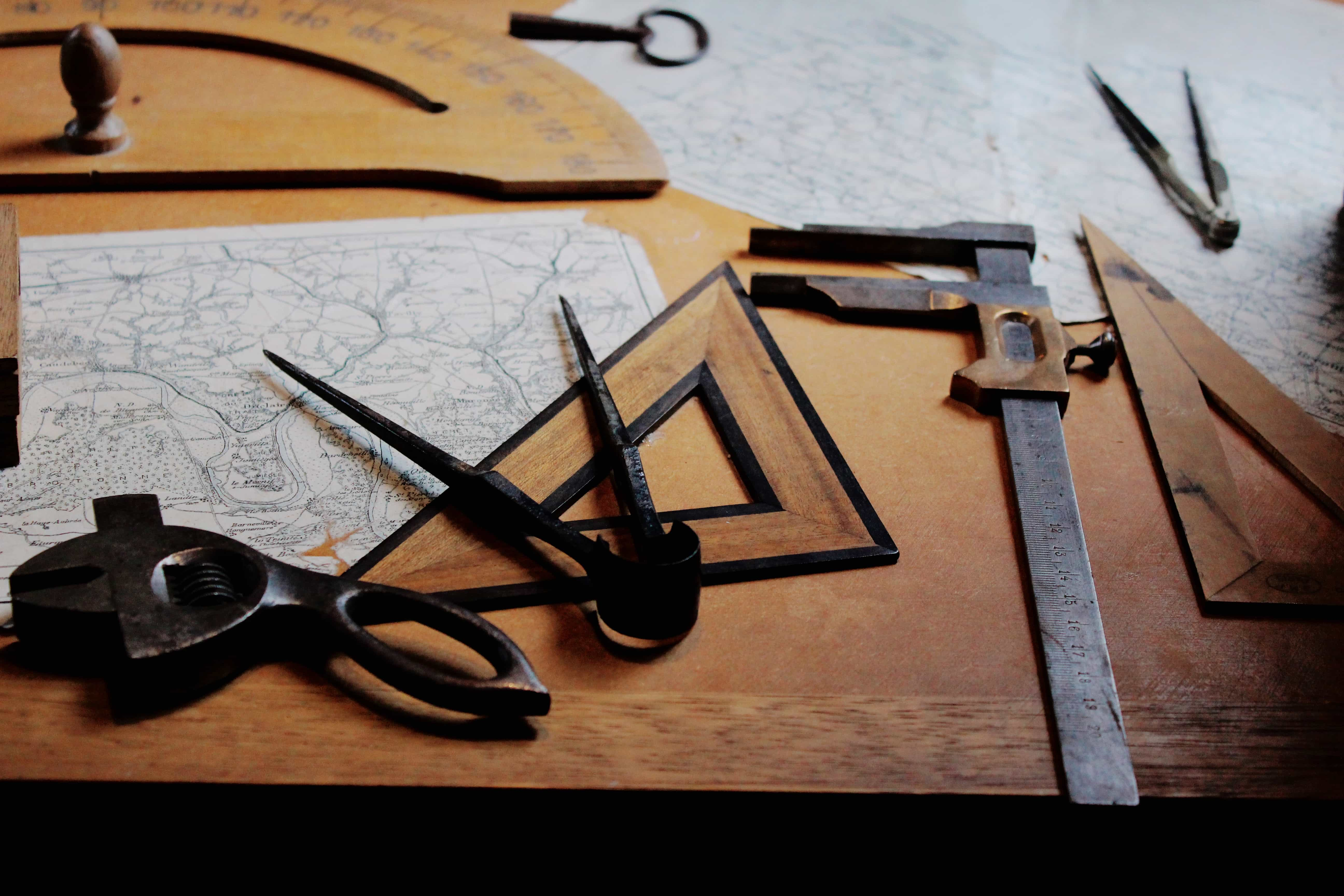 Imagem mostra uma série de ferramentas de medição sobre uma mesa de madeira. Entre elas, três esquadros, de tipos diferentes.