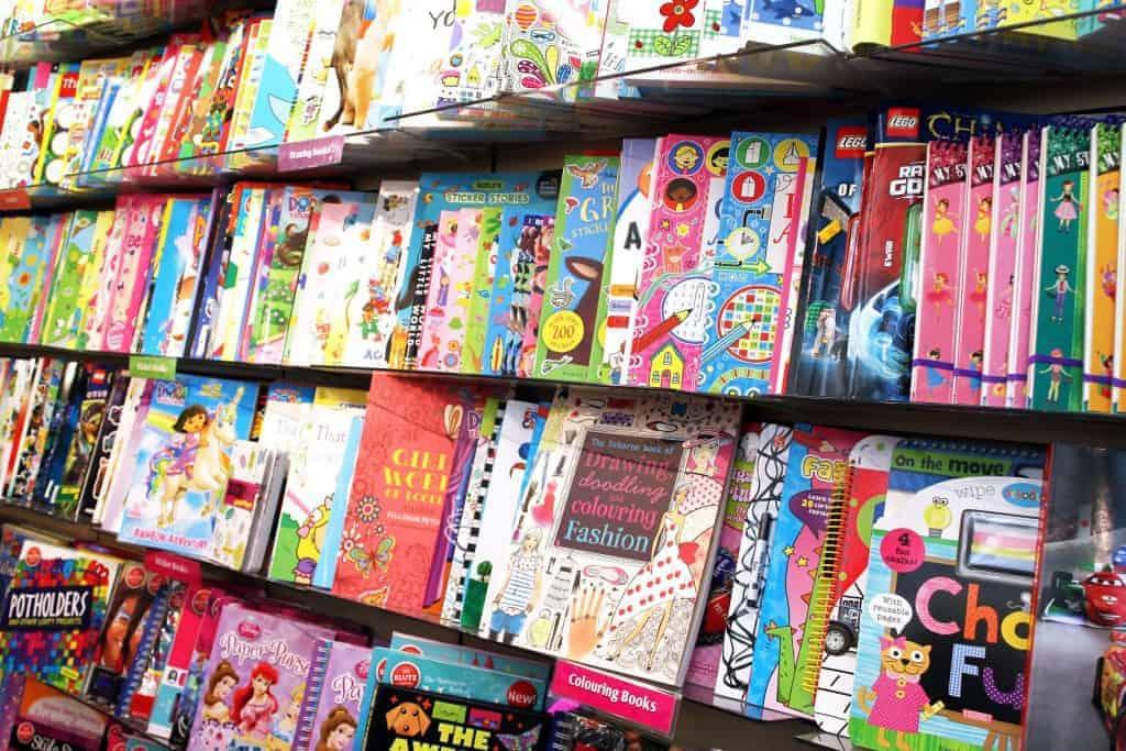 Na foto quatro prateleiras repletas de livros infantis.