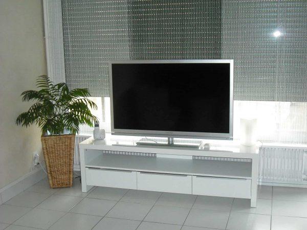 Imagem mostra sala com estante para TV branca com nicho e três gavetas.
