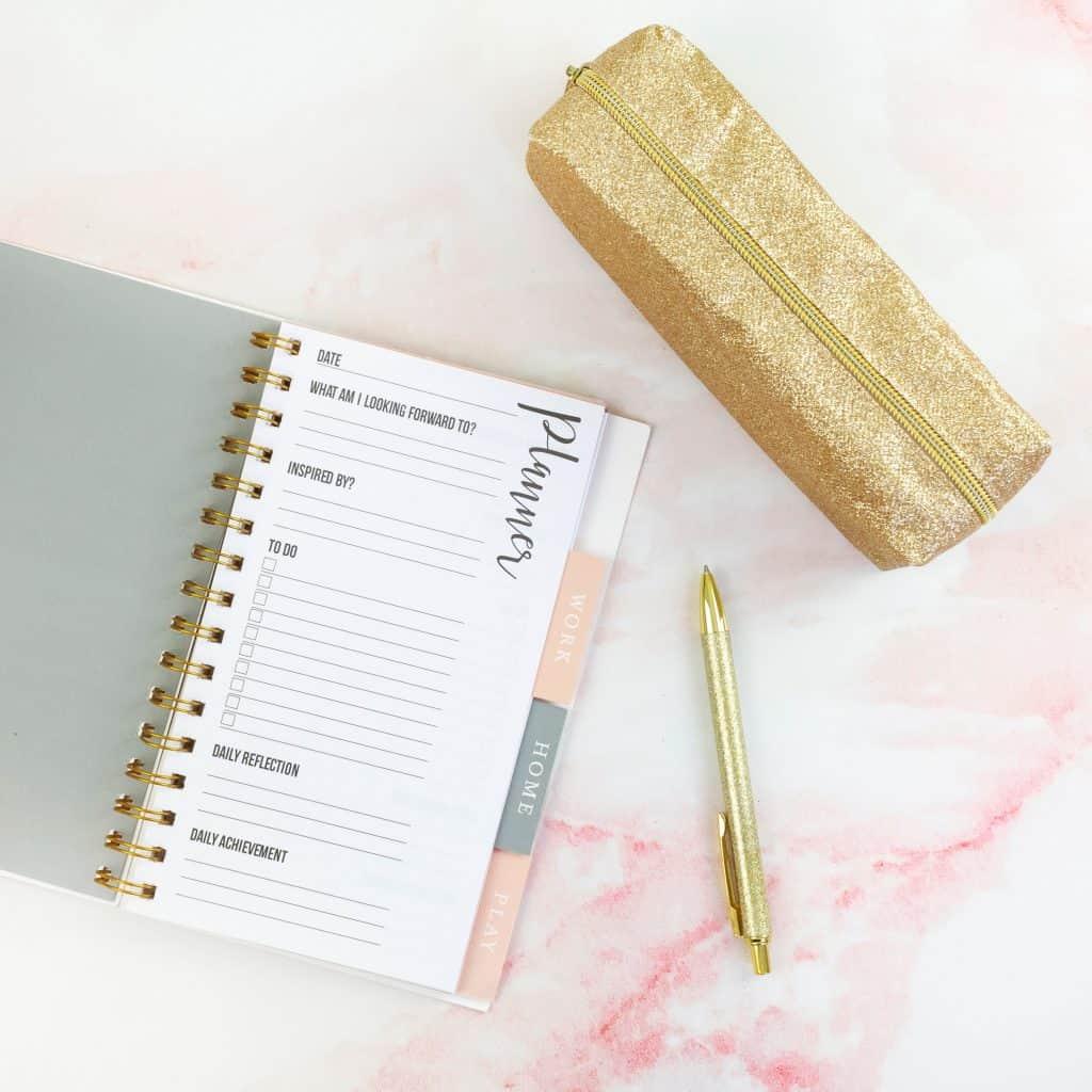 Agenda, caneta e estojo dourado.