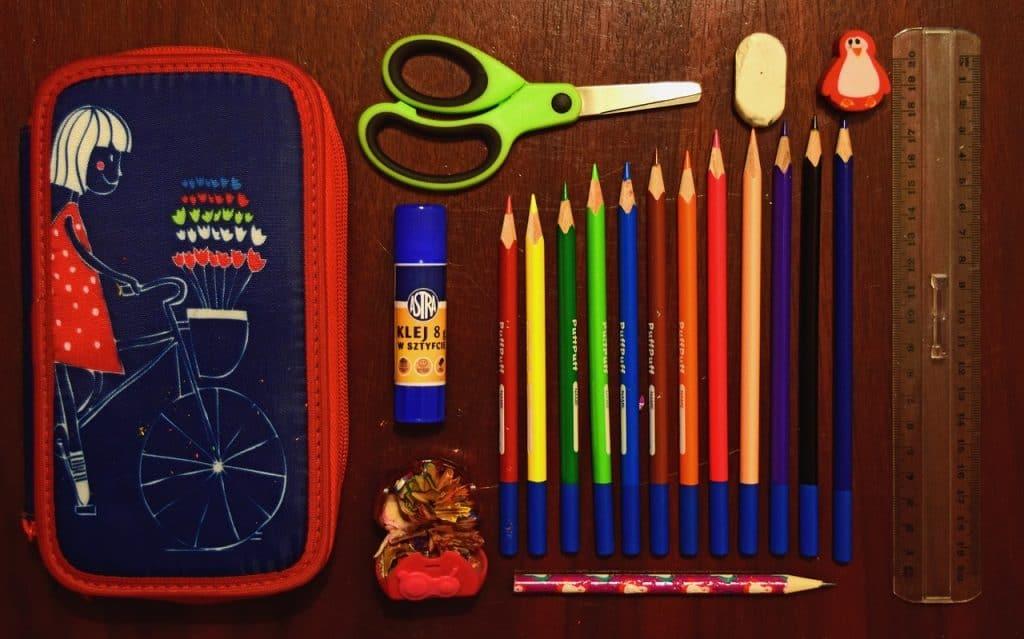 Estojo com lápis de cor, cola, tesoura, régua e borracha.