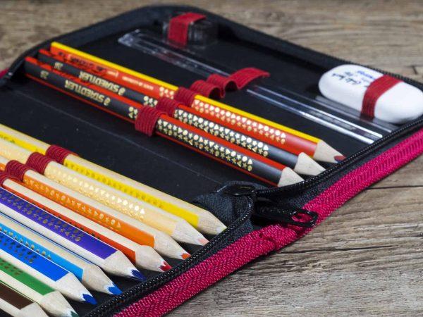Estojo escolar com lápis de cor, lápis grafite, apontador, régua e borracha.