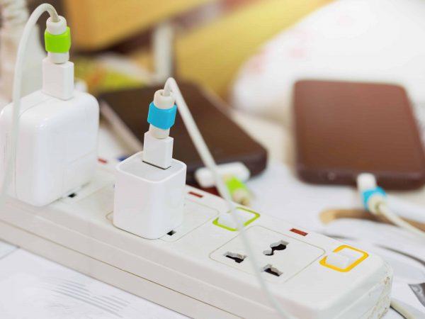 Régua de energia com carregadores usando protetores de cabo coloridos.