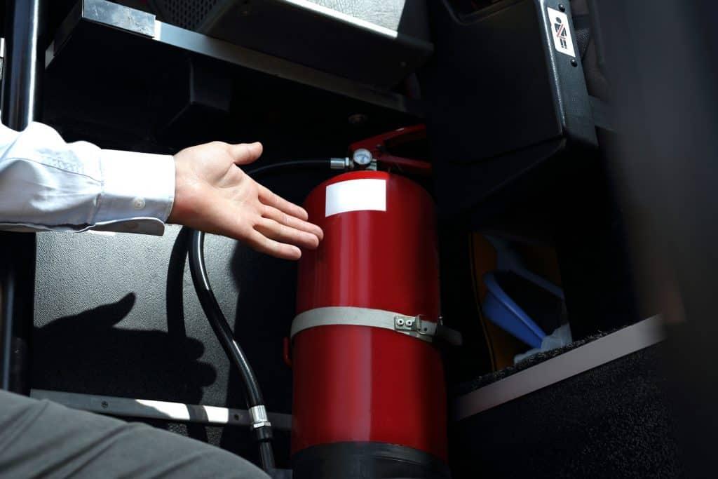 Uma mão mostrando um extintor preso dentro de um ônibus.