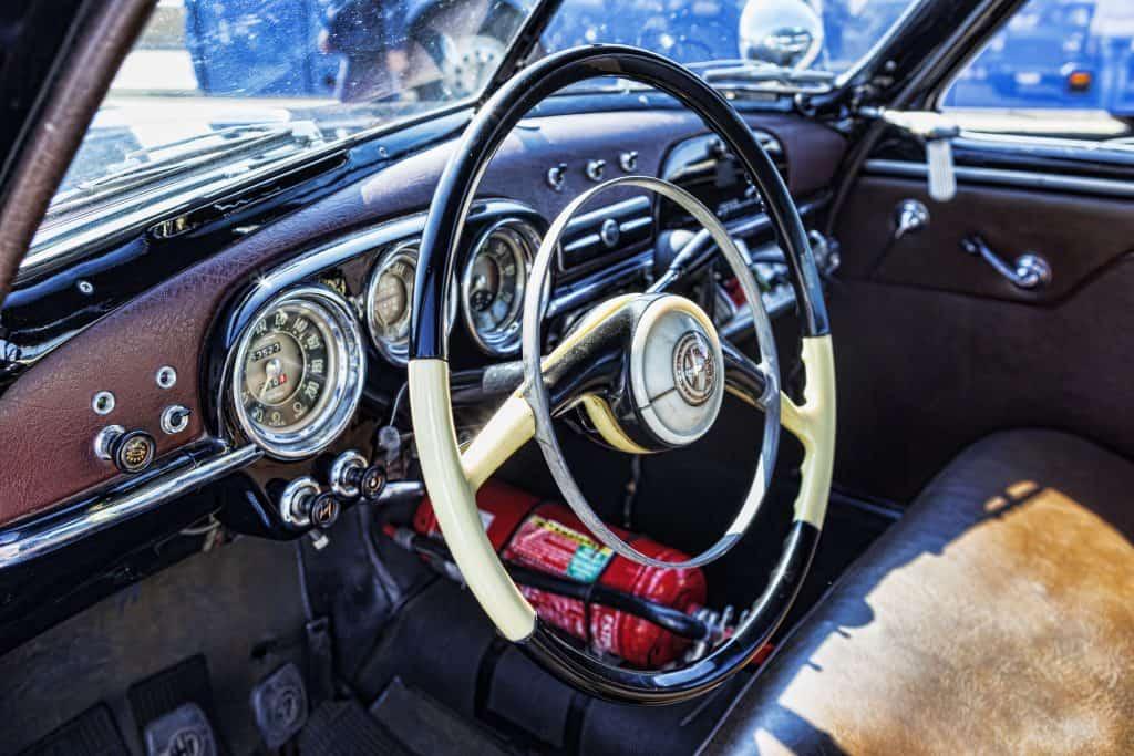 Um extintor instalado embaixo do banco para passageiro da frente em um carro com decoração clássica na parte interior.